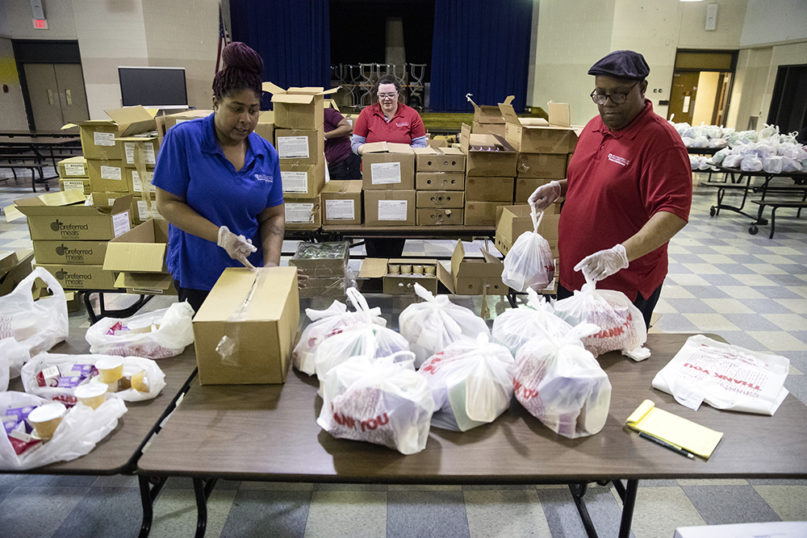 School staff pack grab-and-go meals for distribution to students and families at John H. Webster Elementary School in Philadelphia, Wednesday, March 25, 2020. (AP Photo/Matt Rourke)