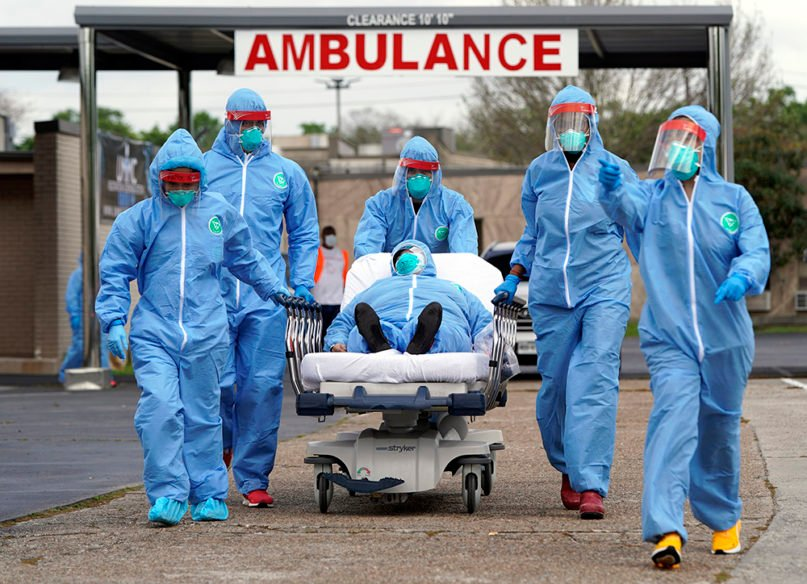 A person is taken on a stretcher into the United Memorial Medical Center after going through testing for COVID-19 on March 19, 2020, in Houston. (AP Photo/David J. Phillip)