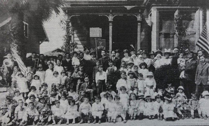 A 1918 church school class smiles with the Rev. Dr. John Misao Yamazaki, vicar, and teachers outside the Mariposa Avenue home used for Sunday services by St. Mary's Episcopal Church, Los Angeles. Photo courtesy of the Episcopal Diocese of Los Angeles