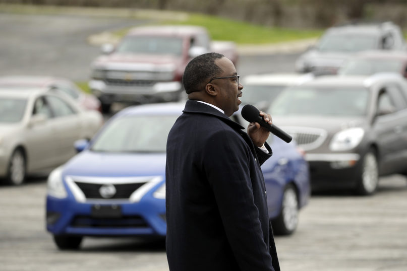 Pastor W.R. Starr II preaches during a drive-in Easter Sunday service, while churchgoers listen from their cars in the parking lot, at the Faith City Christian Center on April 12, 2020, in Kansas City, Kansas. With coronavirus prevention measures shuttering houses of worship, some pastors across the country are urging parishioners to use their cars to safely bring their communities closer together. (AP Photo/Charlie Riedel)