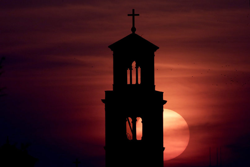 Our Lady of Sorrows Catholic Church is silhouetted against the rising sun in Kansas City, Mo., Wednesday, April 8, 2020. With Easter Sunday in several days, many churches are looking for ways to celebrate the occasion in light of stay-at-home orders and restrictions on gathering in an effort to slow the spread of the new coronavirus. (AP Photo/Charlie Riedel)