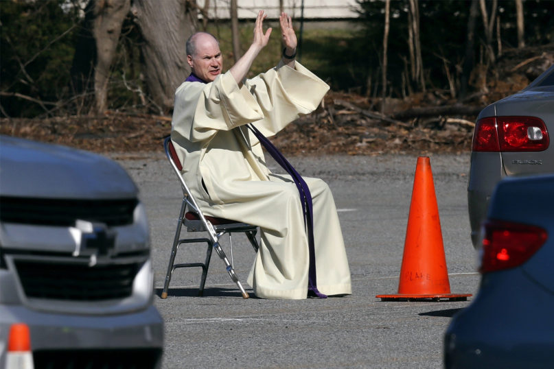 The Rev. Brian Mahoney raises his arms during a confession held in the parking lot, due to the coronavirus outbreak, at St. John the Evangelist Catholic Church in Chelmsford, Massachusetts, on April 6, 2020. After Massachusetts Gov. Charlie Baker issued an emergency order prohibiting most gatherings of over 10 people due to the coronavirus, the parish moved its confessional outdoors with drive-up service. (AP Photo/Charles Krupa)