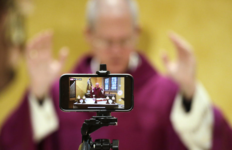 A cellphone is used to livestream Mass by Archbishop Paul D. Etienne at St. James Cathedral, the Cathedral for the Catholic Archdiocese of Seattle, where open Masses have been suspended because of the coronavirus outbreak, March 28, 2020, in Seattle. (AP Photo/Elaine Thompson)