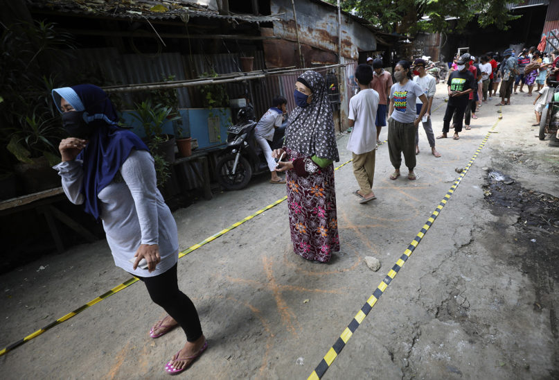 Residents practice social distancing as they queue for donated food during the coronavirus pandemic in a slum area of Jakarta, Indonesia, on April 22, 2020. Indonesian President Joko Widodo has banned people from returning to their hometowns to celebrate the Muslim Eid al-Fitr holiday amid warnings from health experts that the country could face an explosion of coronavirus cases unless the government takes stricter measures. (AP Photo/Dita Alangkara)