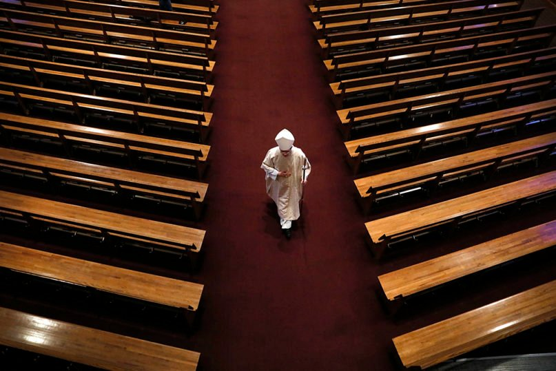 Bishop William Joensen proceeds down the main aisle at the conclusion of Holy Thursday Mass in a near empty St. Ambrose Cathedral, Thursday, April 9, 2020, in Des Moines, Iowa. (AP Photo/Charlie Neibergall)