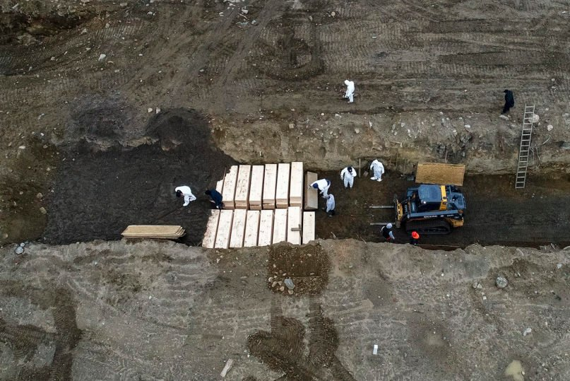 Workers wearing personal protective equipment bury bodies in a trench on Hart Island for temporary internment on April 9, 2020, in the Bronx borough of New York. The strip of land in Long Island Sound has long served as the city's potter's field. (AP Photo/John Minchillo)