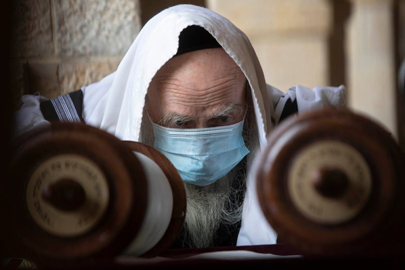 A Jewish man wears a face mask to curb the spread of the coronavirus as he reads from a Torah scroll at the Western Wall, the holiest site where Jews can pray in Jerusalem's Old City, on April 10, 2020. (AP Photo/Sebastian Scheiner)