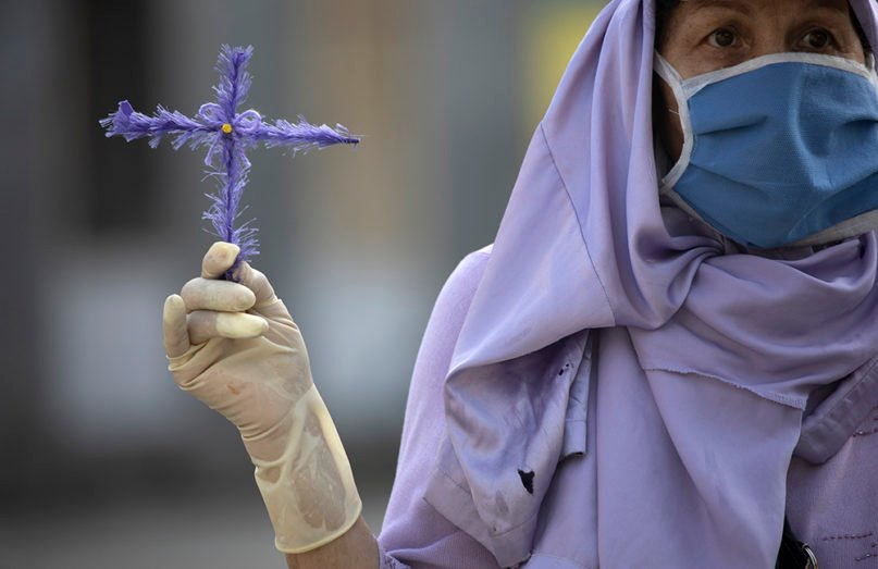 """Wearing a face mask, a devotee of the """"Nazareno de San Pablo"""" holds a cross as she watches a statue of Jesus pass by in a vehicle during Holy Week commemorations in Caracas, Venezuela, on April 8, 2020. The annual procession, in which pilgrims normally take to the streets, was not allowed this year due to quarantine laws to help contain the spread of the new coronavirus, so the Catholic Church is driving the religious icon around the capital for people to see from their homes. (AP Photo/Ariana Cubillos)"""