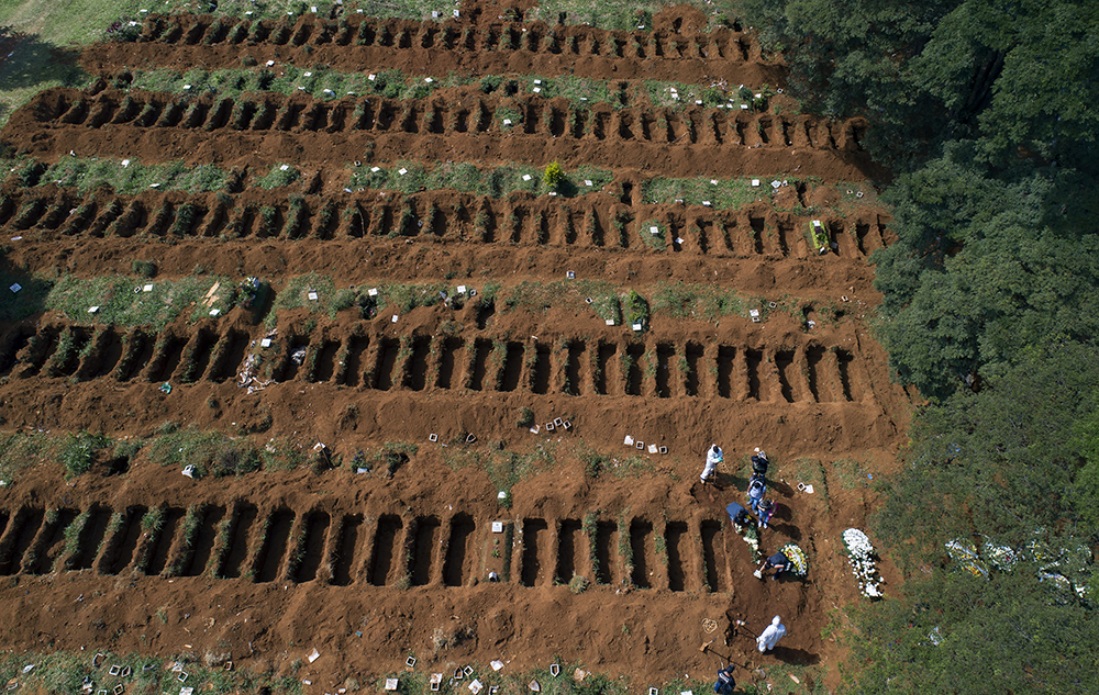 Cemetery workers in protective clothing bury a person at the Vila Formosa cemetery in Sao Paulo, Brazil, on April 1, 2020. Vila Formosa cemetery, the largest in Latin America, has had a 30% increase in the number of burials amid the spread of the new coronavirus, according to the cemetery's administration. (AP Photo/Andre Penner)