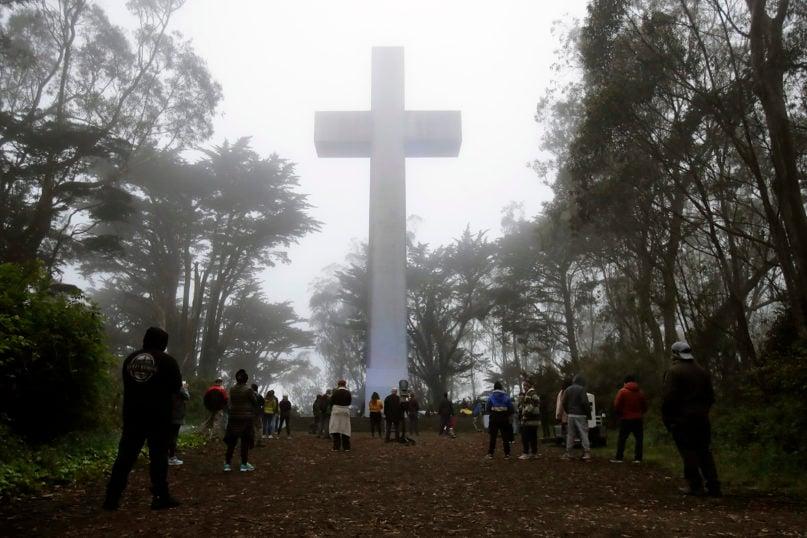 People gather at the Mount Davidson cross in San Francisco, Sunday, April 12, 2020. (AP Photo/Jeff Chiu)