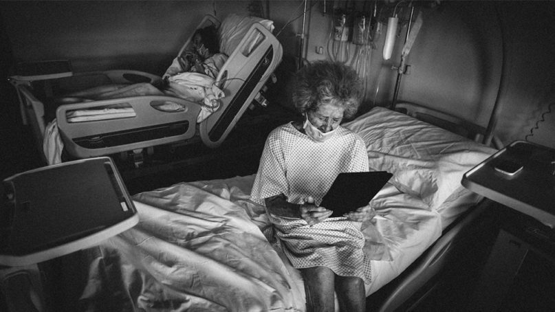 A woman uses a tablet to video chat from San Bortolo Hospital in Vicenza, northern Italy. Photo by Mauro Pozzer