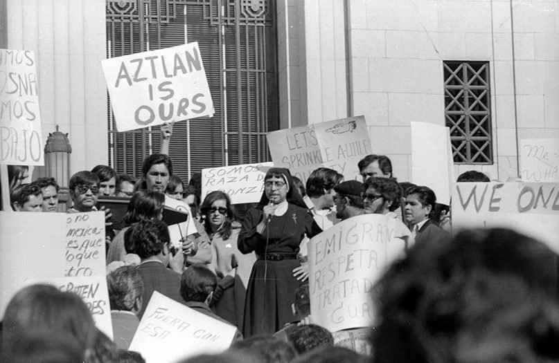 A nun speaks to protesters in front of the California State Building in downtown Los Angeles at an immigration march against the Dixon-Arnett Act on Jan. 22, 1972. Photo by Pedro Arias/La Raza Photograph Collection. Courtesy of the UCLA Chicano Studies Research Center.