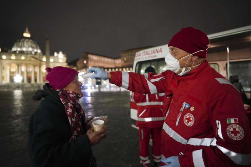 A Red Cross volunteer checks the temperature of a homeless woman while distributing food and disinfectants in front of St. Peter's Square in Rome on March 25, 2020. (AP Photo/Andrew Medichini)