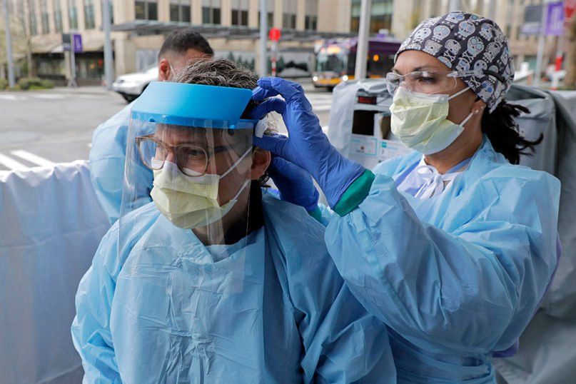 Tilliesa Banks, right, an emergency services nurse at Harborview Medical Center in Seattle, helps a colleague put on a medical face shield prior to their shift in a triage tent outside the Harborview emergency department used to intake arriving patients who have respiratory symptoms, Thursday, April 2, 2020. The face shield was 3-D printed and assembled by a member of a network of volunteers using a design approved and hosted by the U.S. National Institutes of Health. (AP Photo/Ted S. Warren)