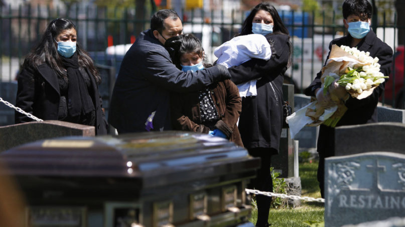 In this May 12, 2020, photo, the Rev. Joseph Dutan comforts his niece, Valerie Dutan, at the funeral of his father, Manuel Dutan, at St. John's Cemetery in the Queens borough of New York. Within one month, Dutan experienced the loss of his father and a fellow cleric, whom he considered a mentor. (AP Photo/Jessie Wardarski)