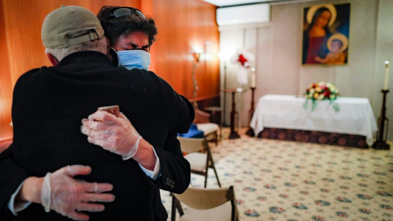 Leonardo Cabaña cries in the arms of his friend Raphael Benevides beside the casket of his father, Héctor Miguel Cabaña, who died of COVID-19, before the funeral home service led by the Rev. Fabian Arias, on May 11, 2020, in the Brooklyn borough of New York. In hard-hit New York City, the coronavirus outbreak has taken a particularly heavy toll on Hispanic communities. (AP Photo/John Minchillo)