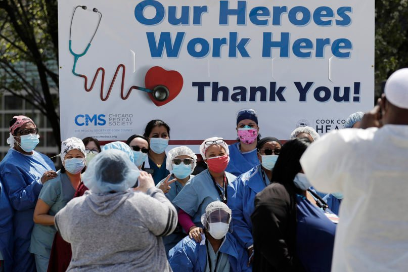 Health care workers at John H. Stroger Jr. Hospital of Cook County take photos with co-workers after they watched the U.S. Navy's Blue Angels flight demonstration squadron fly over in Chicago on May 12, 2020. The flyover was a salute to first responders in the wake of the coronavirus pandemic. (AP Photo/Nam Y. Huh)