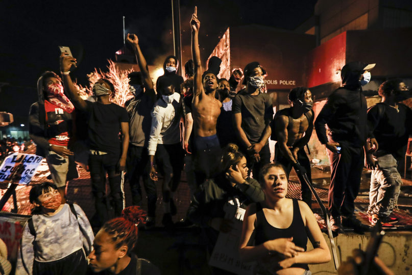 Protesters demonstrate outside of a burning Minneapolis 3rd Police Precinct, Thursday, May 28, 2020, in Minneapolis. Protests over the death of George Floyd, a black man who died in police custody Monday, broke out in Minneapolis for a third straight night. (AP Photo/John Minchillo)