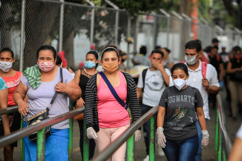 Workers wear masks as a protection against the spread of the new coronavirus as they leave work in Managua, Nicaragua, on May 11, 2020. President Daniel Ortega's government has stood out for its refusal to impose measures to halt the new coronavirus for more than two months since the disease was first diagnosed in Nicaragua. Now, doctors and family members of apparent victims say, the government has gone from denying the disease's presence in the country to actively trying to conceal its spread. (AP Photo/Alfredo Zuniga)
