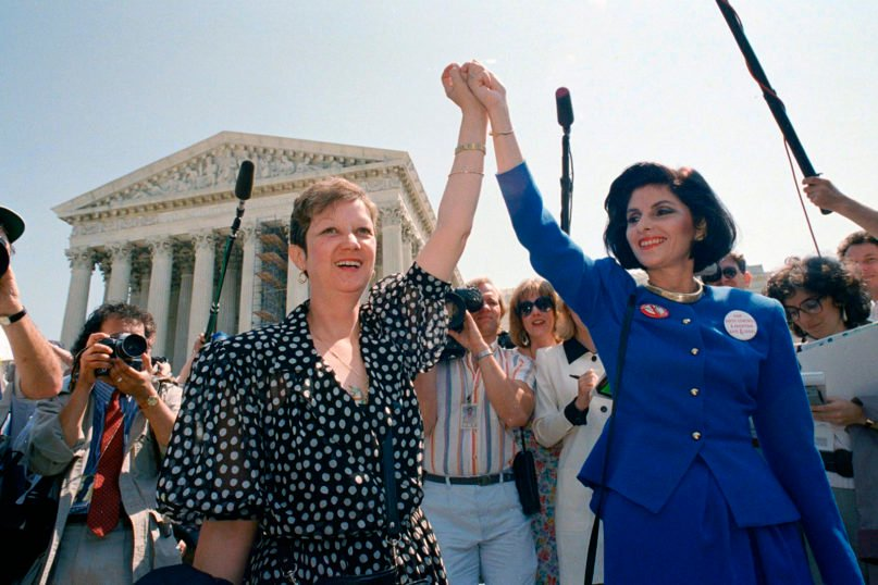 """In this April 26, 1989, file photo, Norma McCorvey, Jane Roe in the 1973 Roe v. Wade court case, left, and her attorney Gloria Allred hold hands as they leave the Supreme Court building in Washington after sitting in while the court listened to arguments in a Missouri abortion case. Three years after her death of heart failure at age 69, the woman better known as """"Jane Roe"""" is making headlines again. In a documentary being released Friday, Norma McCorvey tells the audience that her support for the anti-abortion cause was an act all along. The documentary """"AKA Jane Roe"""" premieres Friday on FX.  (AP Photo/J. Scott Applewhite, File)"""