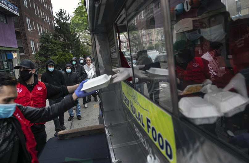 People queue up for free food in the Bay Ridge neighborhood of Brooklyn, New York, on Thursday, April 30, 2020. Various community groups including Muslims Giving Back (in red vests on left) and Gyro King have started serving halal hot meals to help Muslims observing the holy month of Ramadan break fast. Four mobile food trucks are providing this service around New York City as part of efforts to help those affected by the economic contraction caused by the spread of the coronavirus. This service will serve approximately 1,000 meals a day during Ramadan. (AP Photo/Wong Maye-E)