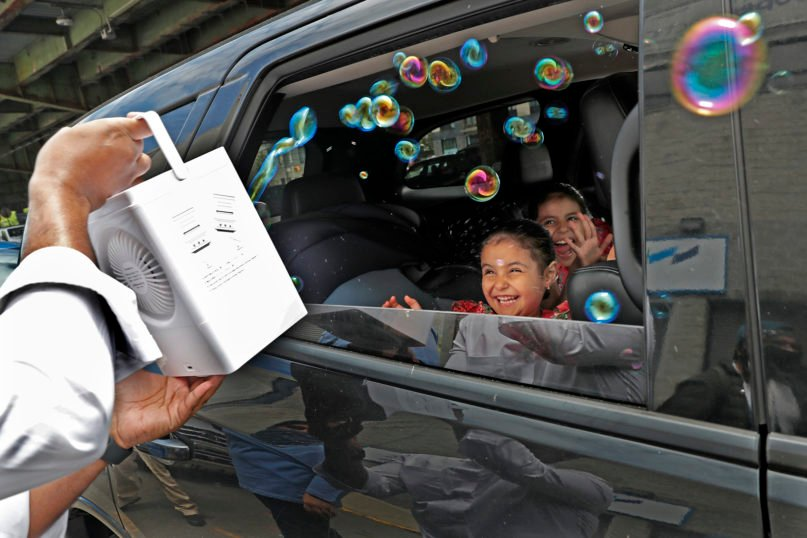Children react from inside their family's car as a volunteer from the Muslim Community Center blows bubbles at them as part of an Eid al-Fitr celebration, marking the end of the fasting month of Ramadan, in the Sunset Park neighborhood of Brooklyn, Sunday, May 24, 2020, in New York. Due to the need for social distancing because of the coronavirus pandemic, the celebration was held as a drive-thru event in which sweets and toys were handout out. (AP Photo/Kathy Willens)