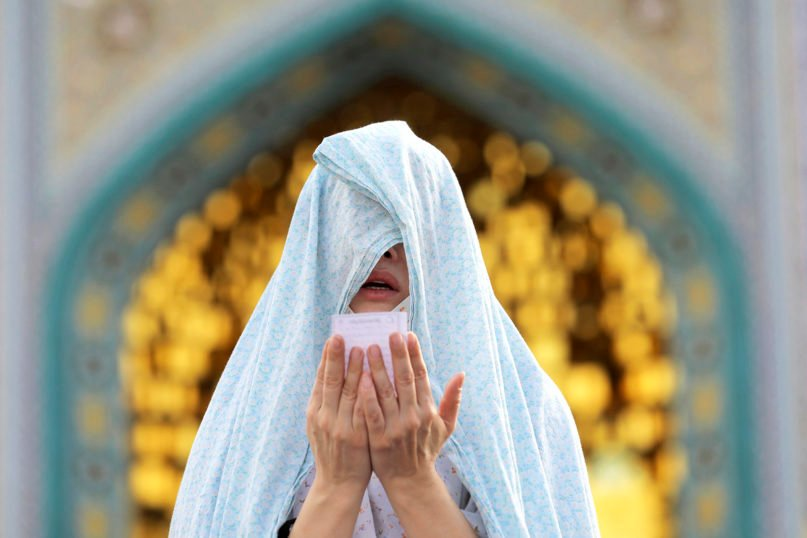 The long shadow of the coronavirus has curtailed worship for millions, including during key holidays for Christians, Jews and Muslims. Here. an isolated worshipper prays during Eid al-Fitr, marking the end of Ramadan in May. (AP Photo/Ebrahim Noroozi)