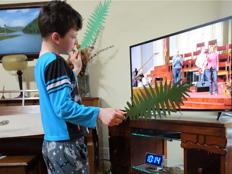 Kagan Kaylor, 8, waves homemade palms during music time while watching the online service of First Baptist Church Jefferson City on Palm Sunday, April 5, 2020, from his home in central Missouri. Photo courtesy of Brian Kaylor