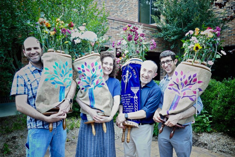 Henry Fuchs, third from left, holds the Tokaj Torah, decorated with a wreath of flowers for the holiday of Shavuot in keeping with Hungarian Jewish tradition, in May 2017. The Tokaj Torah is one of four used by Kehillah Synagogue in Chapel Hill. Photo courtesy of Rabbi Jen Feldman
