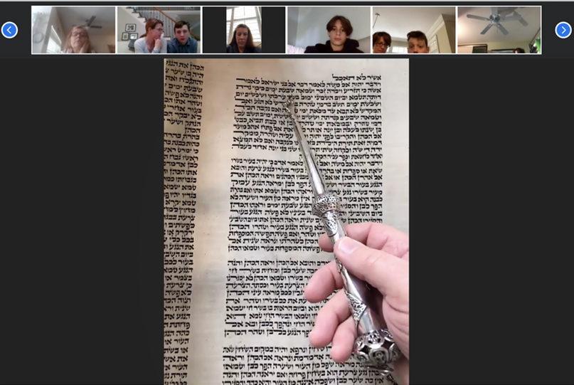 "Henry Fuchs holds a ""yad,"" or silver Torah pointer, to the Tokaj Torah as synagogue members follow along on Zoom, April 25, 2020. Video screenshot by Yonat Shimron"