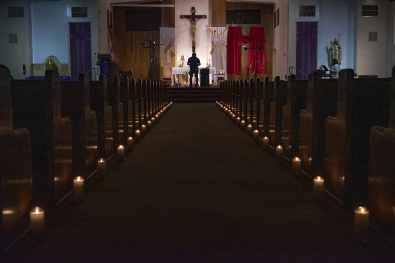 In this April 11, 2020, file photo, a person films pastor Nicolas Sanchez, center left, celebrating Easter Vigil Mass at his church, decorated with candles and pictures sent by his parishioners attached to their pews, at St. Patrick Church in North Hollywood, California. (AP Photo/Damian Dovarganes)