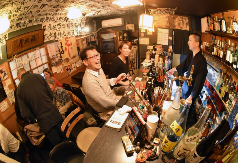 In this March 5, 2020 photo, customers laugh at the Vowz Bar, run by Buddhist priests, in downtown Tokyo. Buddhism suffers from a gloomy image in Japan given its close link to funerals, but some younger priests are trying to rejuvenate the religion by making it more appealing and relevant to daily life through activities such as traditional story-telling, contemporary music, TV show appearances, counseling people considering suicide and hosting customers at such
