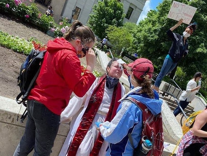 """Ordained United Methodist elder the Rev. Laura Young, center, receives care from bystanders after being pepper sprayed by police during a anti-racism demonstration in Columbus, Ohio, Saturday, May 30, 2020. """"I was pepper sprayed in the face, intentionally, with no warning, by police,"""" she said. """"We as clergy need to be standing with the marginalized … If we're going to put our faith into action, which is a phrase a lot of Methodists like to use, what better way to do it than when it's really needed?"""" Photo by Monica Lewis"""