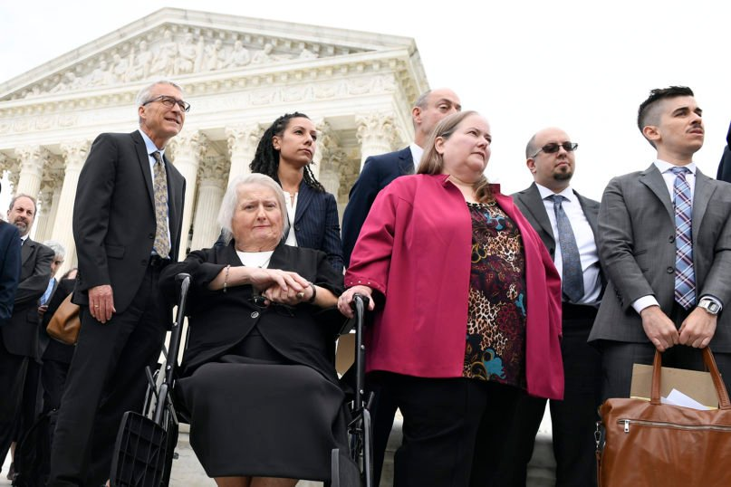 Aimee Stephens, seated, and her wife Donna Stephens, in pink, listen during a news conference outside the Supreme Court in Washington, Tuesday, Oct. 8, 2019. Aimee Stephens lost her job when she told Thomas Rost, owner of the Detroit-area R.G. and G.R. Harris Funeral Homes, that she had struggled with gender identity issues almost her whole life. Stephens died in Michigan in May 2020. (AP Photo/Susan Walsh)