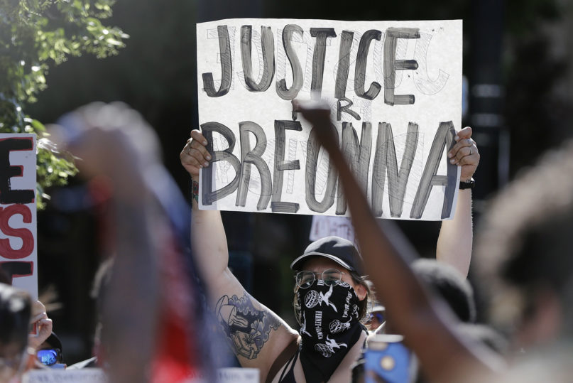A protester holds a sign during a protest June 1, 2020, in Louisville, Kentucky, over the deaths of George Floyd and Breonna Taylor. Taylor, a Black woman, was fatally shot by police in her home in March. (AP Photo/Darron Cummings)