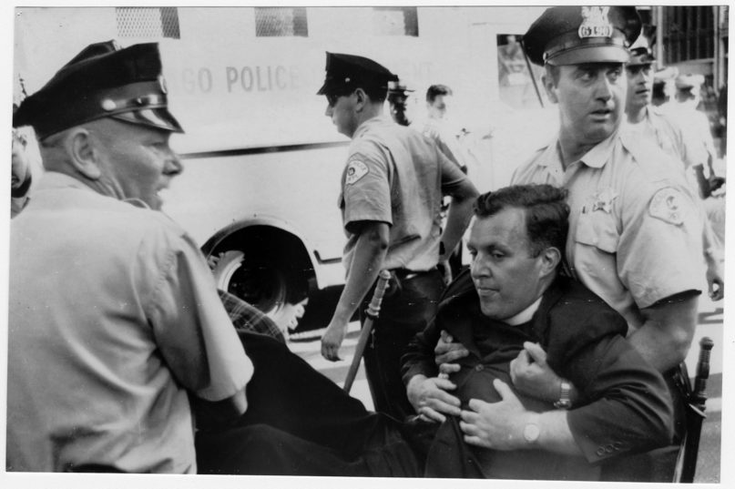The Rev. William Hogan, of St. Martin's Catholic Church in Chicago, is carried off by police in a civil rights demonstration protesting racial imbalance in Chicago's public schools, on June 29, 1965. The priest was one of 80 white and black demonstrators arrested when they held a rush-hour sit-in at a busy intersection outside Chicago City Hall. RNS archive photo
