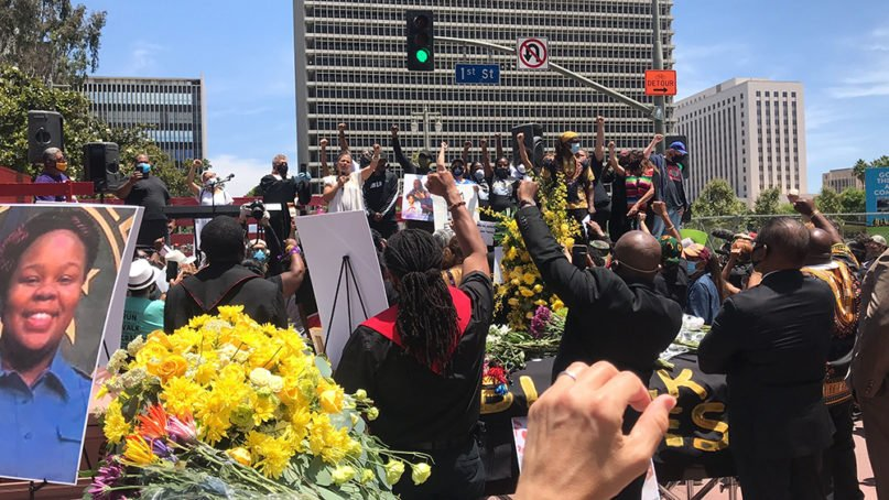 Clergy put their fists in the air as Melina Abdullah, center left, co-founder of Black Lives Matter-Los Angeles, addresses the crowd during an interfaith memorial service for George Floyd, Monday, June 8, 2020, in Los Angeles. RNS photo by Alejandra Molina