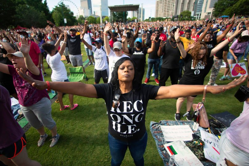 A woman prays during an event hosted by OneRace Movement at Atlanta's Centennial Olympic Park to commemorate Juneteenth on June 19, 2020. OneRace Movement, a religious organization, hosted the event in an effort to call for change and unify across races, classes, denominations and culture. (AP Photo/John Bazemore)