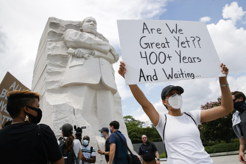 Kimya Hogarth, of Silver Spring, Maryland, holds a sign during a protest in Washington, D.C., at the Martin Luther King Jr. Memorial on June 19, 2020, to mark Juneteenth, the holiday celebrating the day in 1865 that enslaved black people in Galveston, Texas, learned they had been freed from bondage, more than two years after the Emancipation Proclamation. (AP Photo/Jacquelyn Martin)