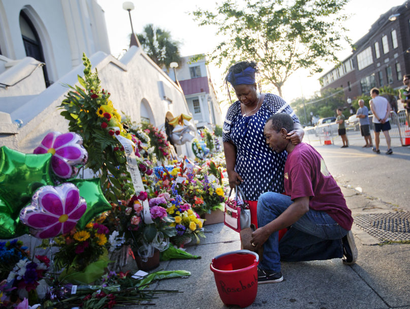 In this June 20, 2015, file photo, Allen Sanders, right, kneels next to his wife, Georgette, both of McClellanville, South Carolina, as they pray at a sidewalk memorial in memory of the shooting victims in front of Mother Emanuel AME Church in Charleston, South Carolina. (AP Photo/David Goldman, File)