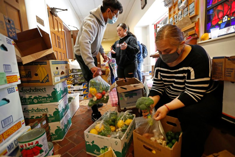 Laura Porras, right, prepares bags of fresh vegetables as Justin Ruiz, 17, left, and Porras' niece Ana Karen Porras, 14, center, help in the vestibule at Lutheran Church of the Good Shepherd in the Bay Ridge neighborhood of the Brooklyn borough of New York on May 12, 2020. The effort, which started two months ago, is coordinated by the Brooklyn Immigrant Community Support mutual aid group, which saw a need for emergency food aid for undocumented immigrants, who couldn't apply for or receive government assistance in the wake of shutdowns caused by concerns over the spread of the new coronavirus. (AP Photo/Kathy Willens)