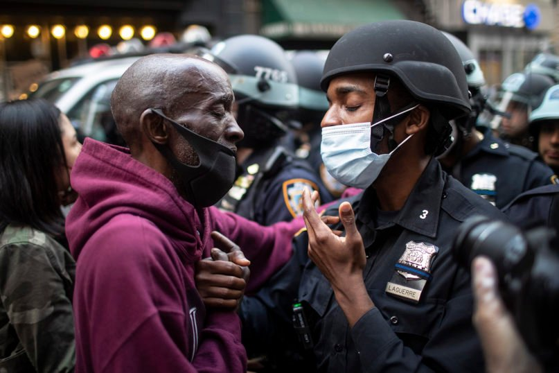 A protester and a police officer shake hands in the middle of a standoff during a solidarity rally calling for justice over the death of George Floyd, on June 2, 2020, in New York. (AP Photo/Wong Maye-E)