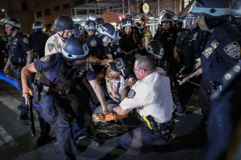 A protester is arrested on Fifth Avenue by New York Police Department officers during a march on June 4, 2020, in the city's Manhattan borough. (AP Photo/John Minchillo)