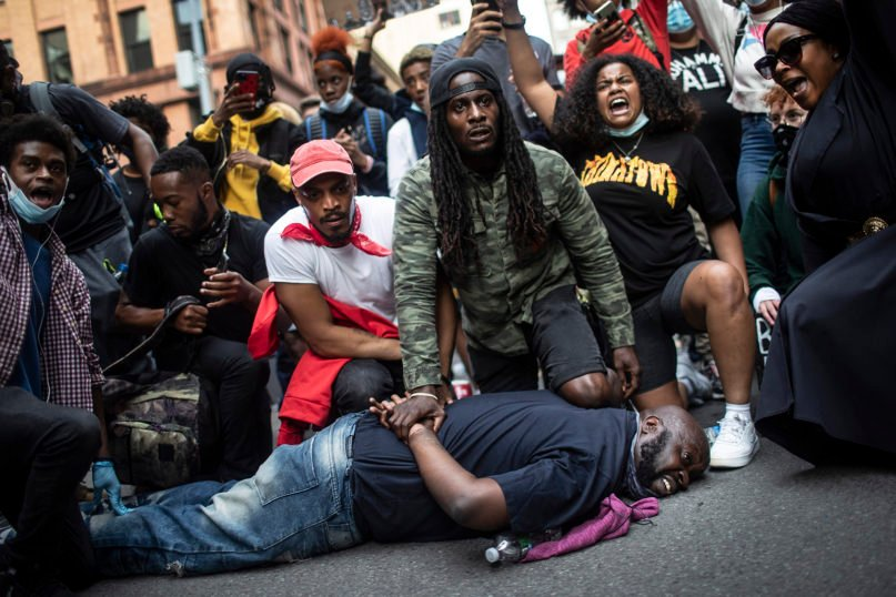 Protesters reenact the scene where George Floyd was restrained by police while marching in a solidarity rally June 2, 2020, in New York calling for justice over his death. Floyd died after being restrained by Minneapolis police officers on May 25. (AP Photo/Wong Maye-E)