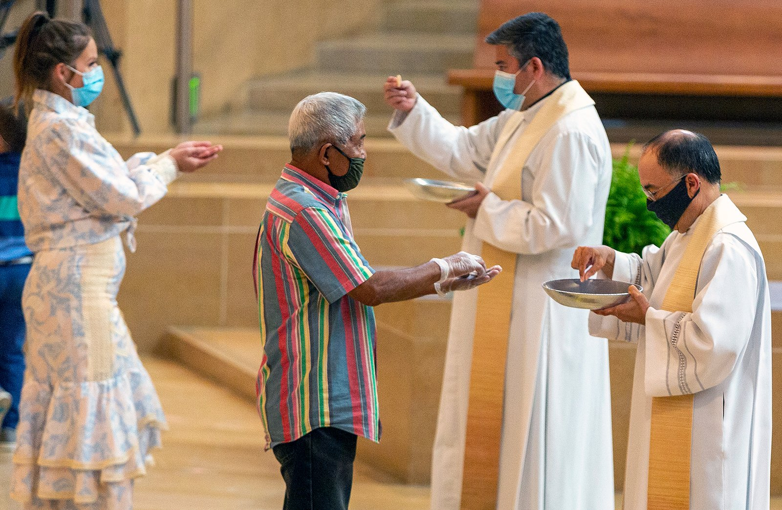 The faithful wear masks and some wear gloves as they receive Communion at the first English Mass with faithful present at the Cathedral of Our Lady of the Angels in downtown Los Angeles, Sunday, June 7, 2020. (AP Photo/Damian Dovarganes)