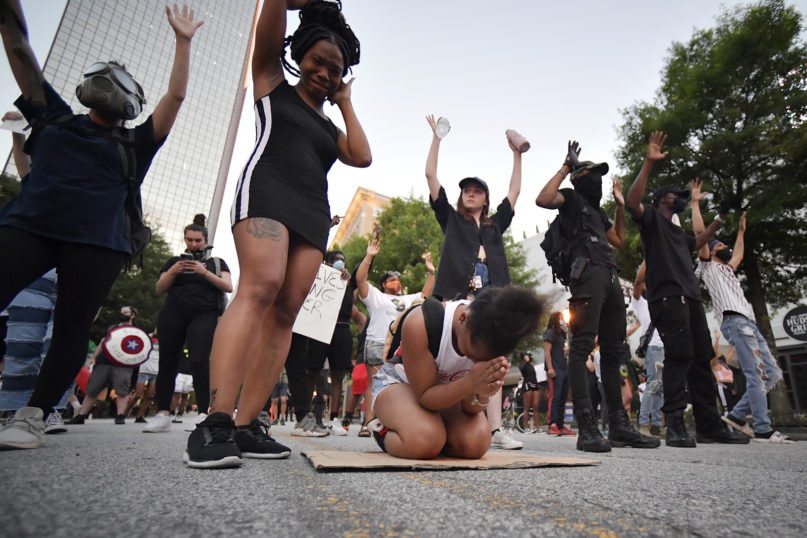 Demonstrators pray during a march May 31, 2020, in Atlanta. Protests spread across the United States after the death of George Floyd, who died after being restrained by Minneapolis police officers on May 25. (AP Photo/Mike Stewart)