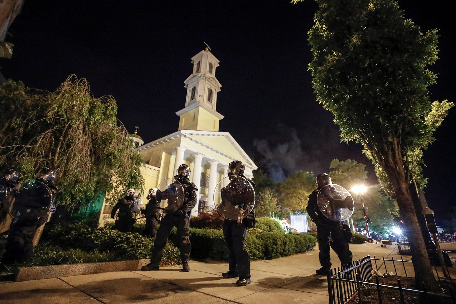 Police form a line in front of St. John's Episcopal Church as demonstrators protest the death of George Floyd, Sunday, May 31, 2020, near the White House in Washington. Floyd died after being restrained by Minneapolis police officers. (AP Photo/Alex Brandon)