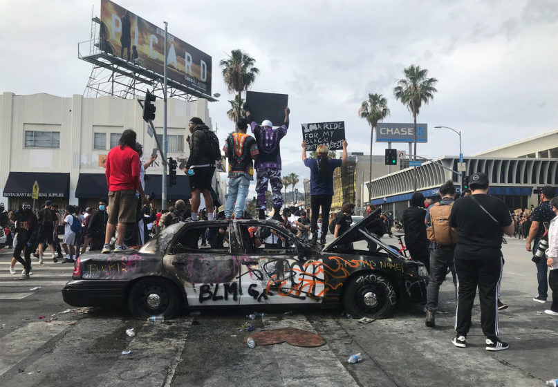 Protesters stand atop a vandalized police car on Beverly Boulevard and Fairfax Avenue on Saturday, May 30, 2020, in Los Angeles. RNS photo by Alejandra Molina