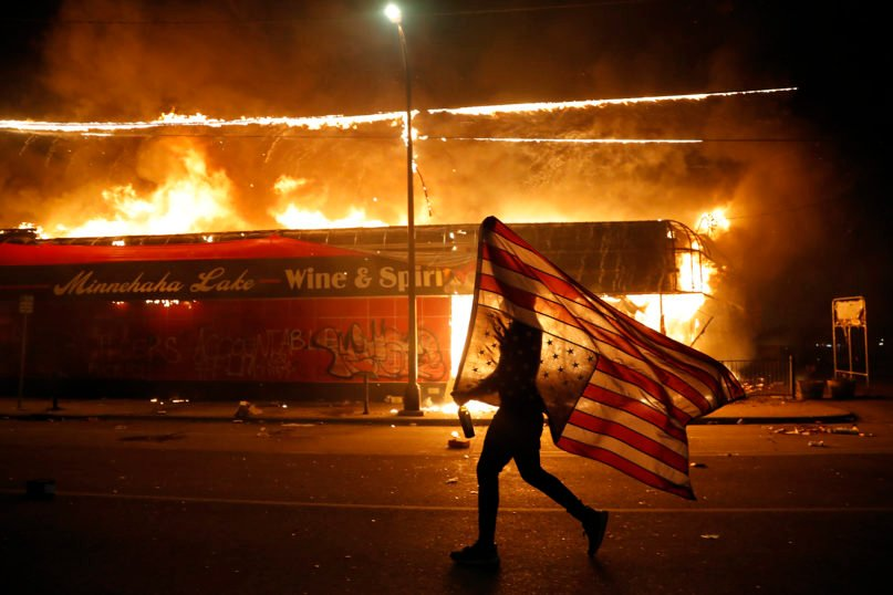 A protester carries a U.S. flag upside down, a sign of distress, next to a burning building May 28, 2020, in Minneapolis. Protests over the death of George Floyd, a Black man who died in police custody on Memorial Day, broke out across the country. (AP Photo/Julio Cortez)