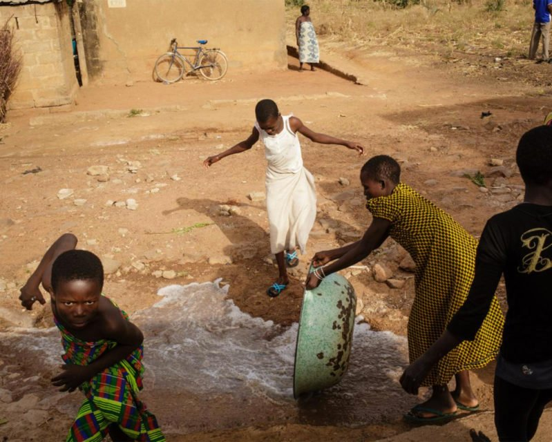Water is thrown in the street in front of a Vivre dans l'Espérance (Living in Hope) orphanage after a bath in Dapaong, Togo. Photo by Julien Pebrel / Myop